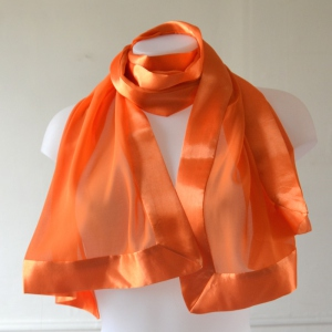 Étole orange en mousseline de soie, bordée de satin.