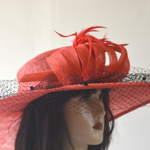 Wide-brimmed coral red wedding hat with black veil and feathers