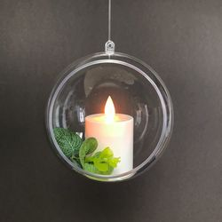 A led votive candle hung in a bubble with eucalyptus