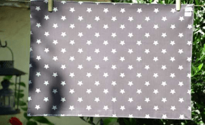 Rectangular place mat, white stars on plum ground plastified linen