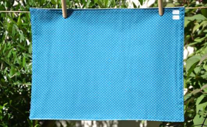 Rectangular place mat, white dotted on turquoise blue ground plastified linen